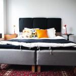 """Sänggaveln är Jörgens egen kreation. Det är egentligen sittdynor från IKEA som han spikat fast i väggen och satt Jean Paul Gaultiers """"dog tags""""/mynt som knappar för att täcka spikarna. Dog tagsen designade Jean Paul Gaultier till Stockholm Pride det år Jörgen arbetade med festivalen."""