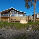 Husen har byggts låga och svarta för att smälta in i miljön. På fasaden sitter en bred limträpanel och trädäcken kommer att bli gråa med åren.