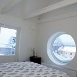 Genom det runda sovrumsfönstret kan makarna Fällgren se ända upp i Frölandsbacken.
