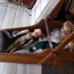 Dockor i en gunga som hänger mellan barnbarnens lilla rum och vardagsrummet.